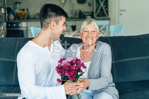 Young man gives flowers to his mother with love