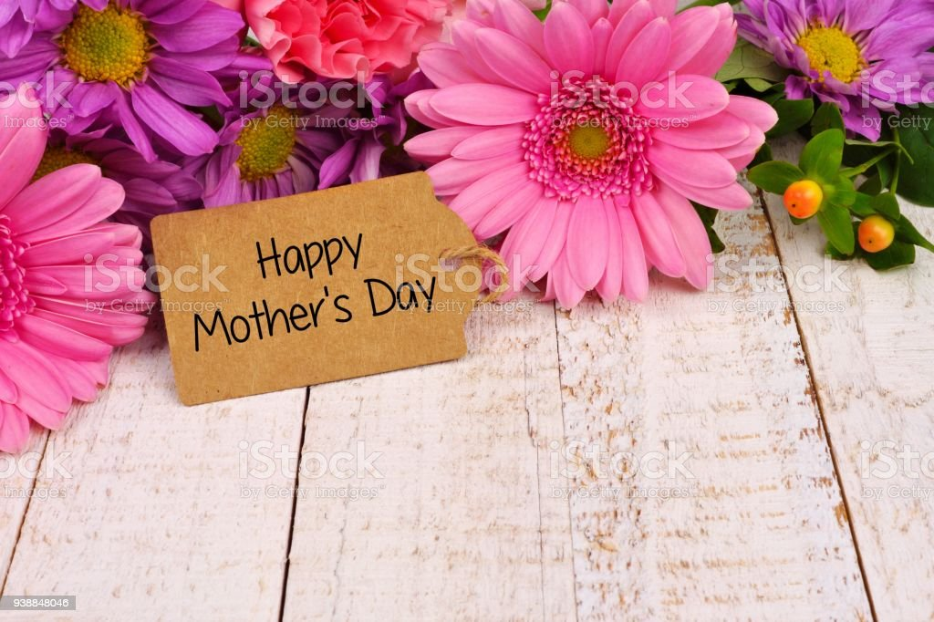 Happy Mothers Day tag close up with flowers over white wood stock photo