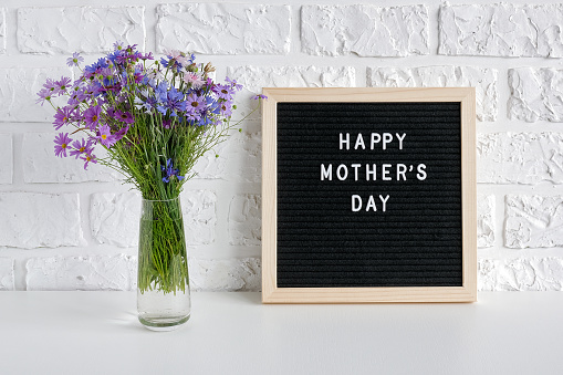istock Happy mothers day text on black letter board and bouquet blue flowers in vase on table against white brick wall. Concept Mothers Day. Template for greeting card, postcard 1167486311