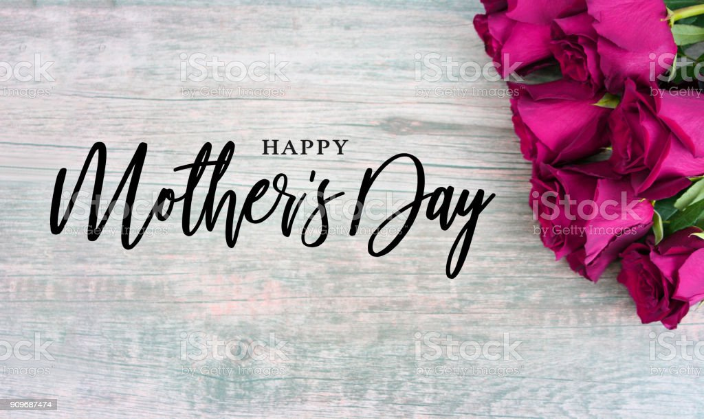 Happy Mother's Day Text with Bright Pink Roses Over Wood stock photo