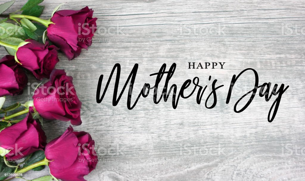 Happy Mother's Day Typography with Bright Pink Roses Over Wood stock photo