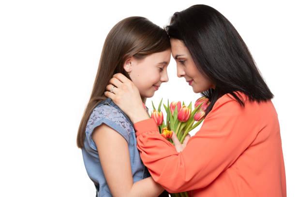 Glücklicher Muttertag, Frauentag oder Geburtstag Hintergrund. Entzückende Mädchen geben Mama Bouquet von rosa Tulpen. Studioporträt einer liebevollen Mutter, die ihre Tochter auf weißem Hintergrund umarmt. – Foto