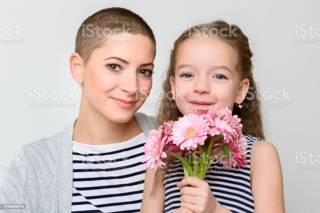 Schönen Muttertag, Frauen Tag oder Geburtstag Hintergrund. Niedliche kleine Mädchen geben Mama, Krebs-Überlebenden, Bouquet von rosa Gerbera Gänseblümchen. Mutter und Tochter lächelnd und Blick in die Kamera. – Foto