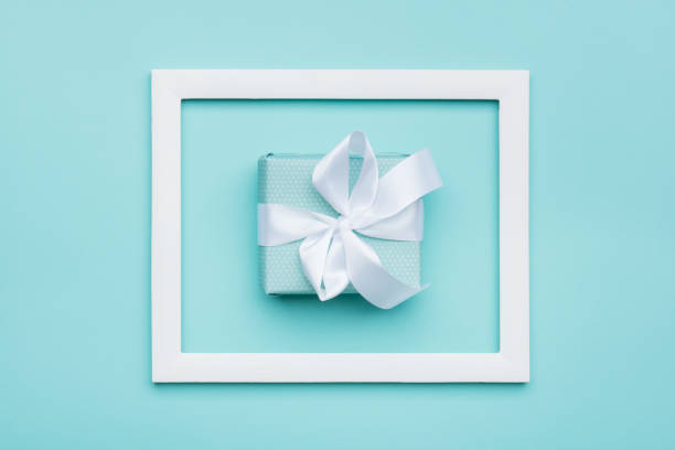 Happy Mother's Day, Women's Day, Valentine's Day or Birthday Background. Pastel Blue Candy Colour flat lay minimal concept with beautifully wrapped present. stock photo