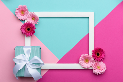 istock Happy Mother's Day, Women's Day, Valentine's Day or Birthday Pastel Candy Colours Background. Floral flat lay minimalism geometric patterns greeting card with a gift box. 911749484
