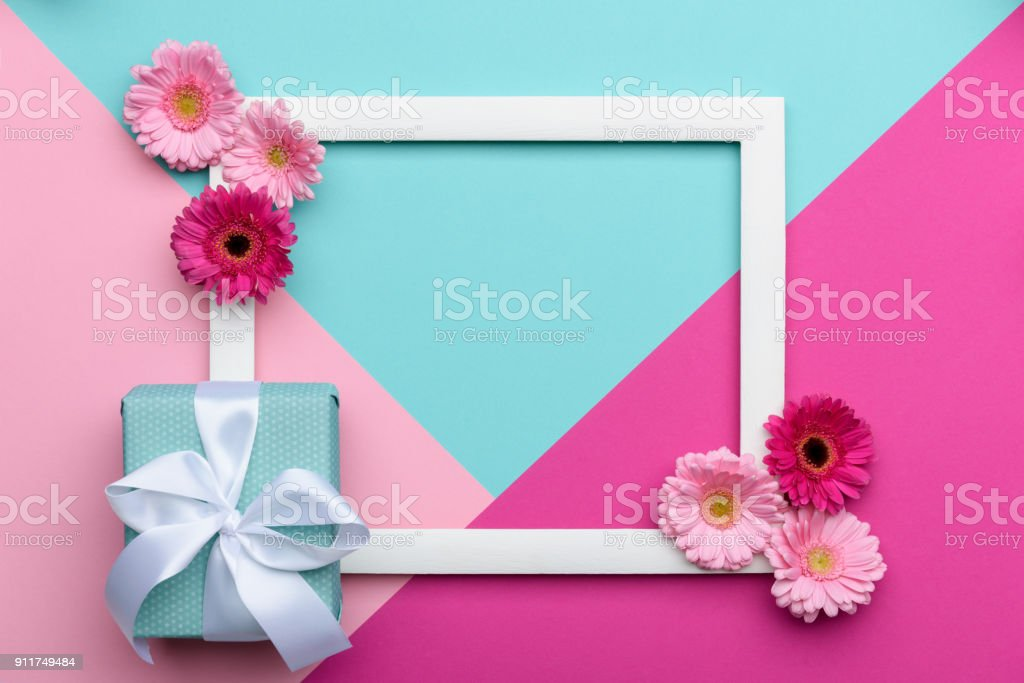 Happy Mother's Day, Women's Day, Valentine's Day or Birthday Pastel Candy Colours Background. Floral flat lay minimalism geometric patterns greeting card with a gift box. stock photo