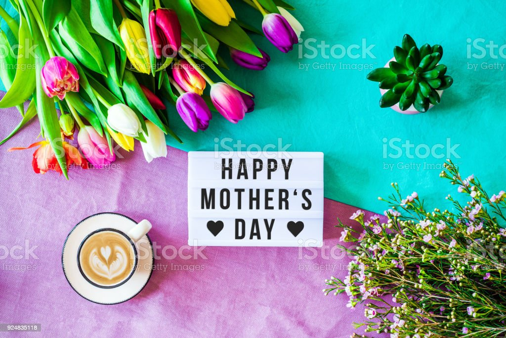 Happy mother's day written in lightbox with spring flowers from above Shot from above as flatlay with happy mother's day message written on light box with coffee and colorful tulips and flowers Backgrounds Stock Photo