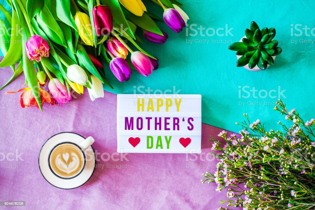 Happy mother's day written in lightbox with spring flowers from above stock photo