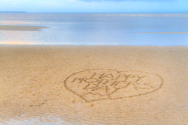 Happy Mother's Day written in the sand stock photo