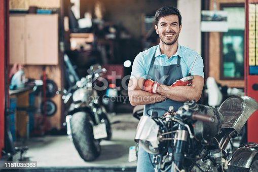 Portrait of a smiling motorcycle mechanic in his workshop