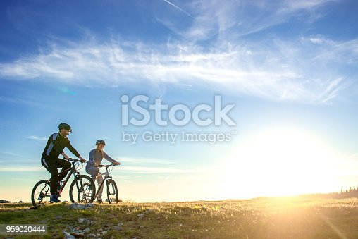 istock Happy mountain bike couple outdoors have fun together on a summer afternoon sunset 959020444