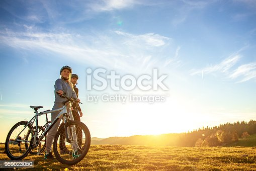 istock Happy mountain bike couple outdoors have fun together on a summer afternoon sunset 959023050