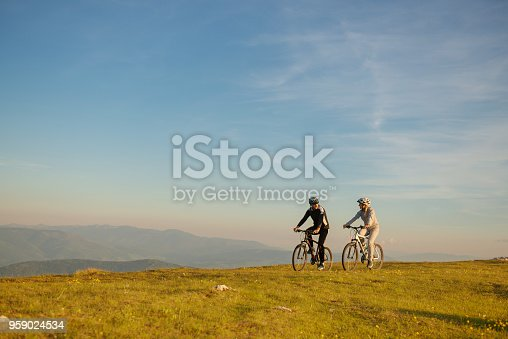 istock Happy mountain bike couple outdoors have fun together on a summer afternoon sunset 959024534