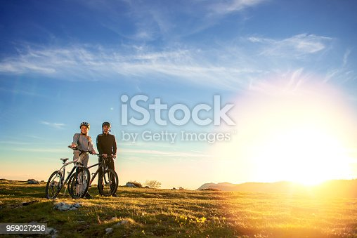 istock Happy mountain bike couple outdoors have fun together on a summer afternoon sunset 959027236