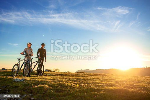 istock Happy mountain bike couple outdoors have fun together on a summer afternoon sunset 959027304
