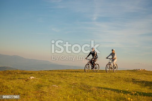 istock Happy mountain bike couple outdoors have fun together on a summer afternoon sunset 959027562
