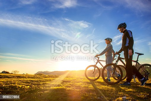 istock Happy mountain bike couple outdoors have fun together on a summer afternoon sunset 959027654