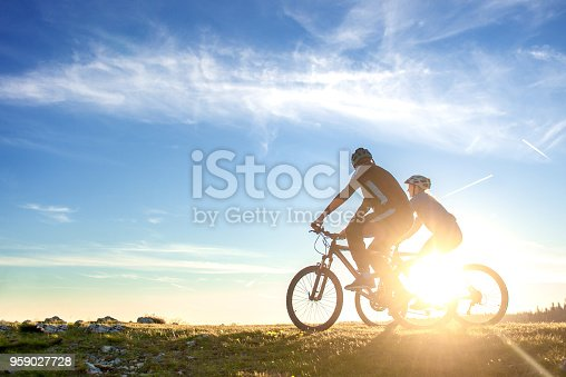 istock Happy mountain bike couple outdoors have fun together on a summer afternoon sunset 959027728