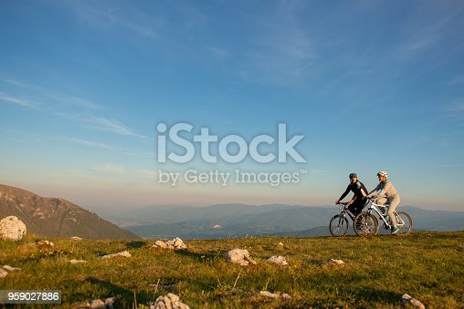 istock Happy mountain bike couple outdoors have fun together on a summer afternoon sunset 959027886