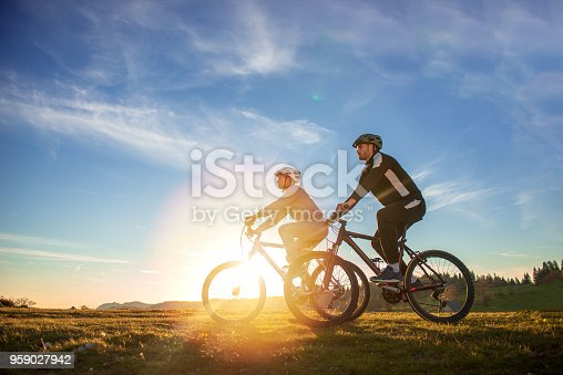 istock Happy mountain bike couple outdoors have fun together on a summer afternoon sunset 959027942