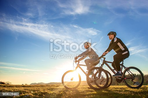 istock Happy mountain bike couple outdoors have fun together on a summer afternoon sunset 959028462