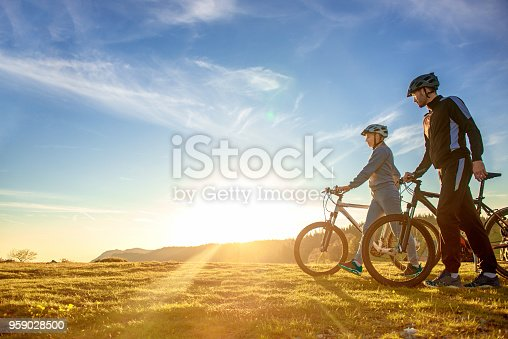 istock Happy mountain bike couple outdoors have fun together on a summer afternoon sunset 959028500