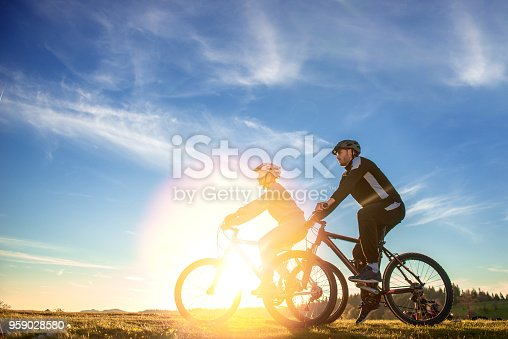 istock Happy mountain bike couple outdoors have fun together on a summer afternoon sunset 959028580