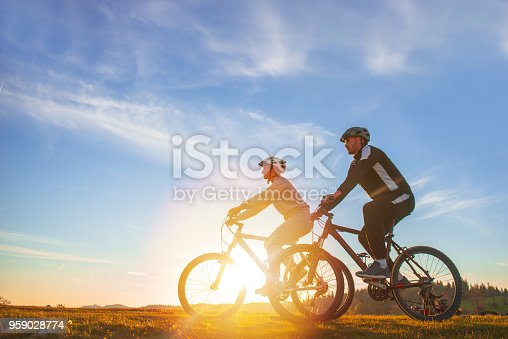 istock Happy mountain bike couple outdoors have fun together on a summer afternoon sunset 959028774