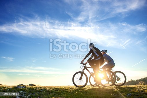 Happy mountain bike couple outdoors have fun together on a summer afternoon sunset.