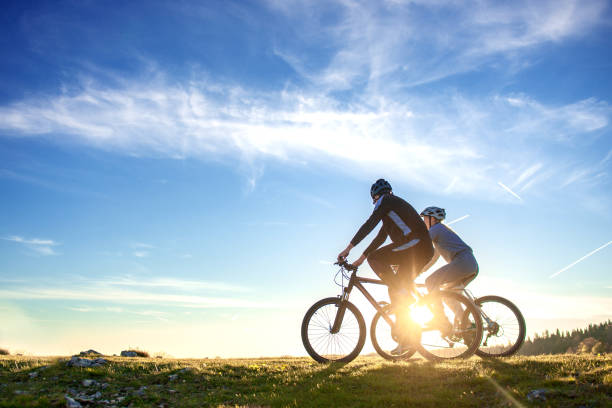 Happy mountain bike couple outdoors have fun together on a summer afternoon sunset stock photo