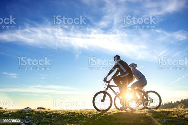 Photo of Happy mountain bike couple outdoors have fun together on a summer afternoon sunset