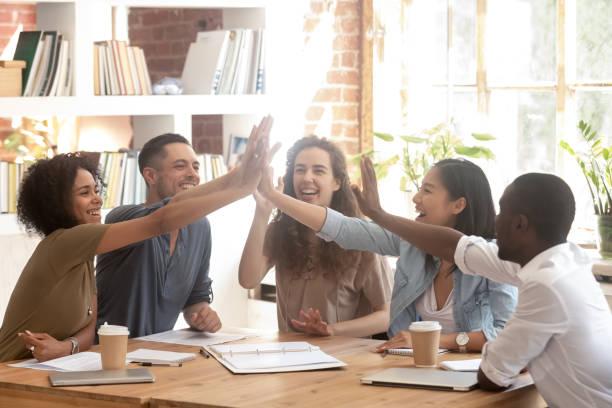 happy multi-etnische business team join handen geven hoge vijf - kleine groep mensen stockfoto's en -beelden