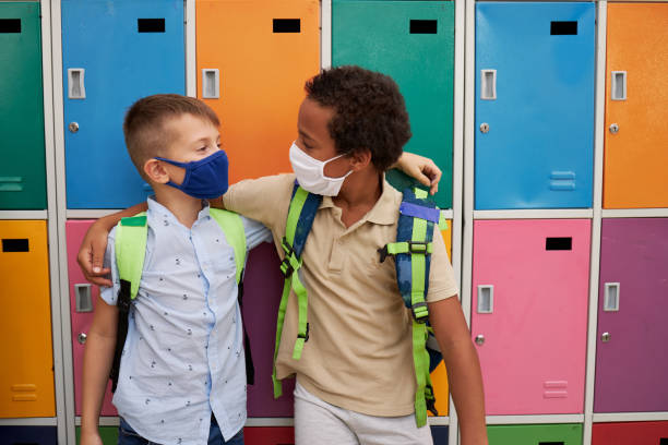 Happy multi ethnic male friends hugging while wearing protective face mask in the school stock photo