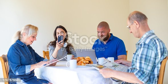 istock Happy multi generational family reading news in the morning while having breakfast, focus on young people - digital dementia and overuse of digital technology concept 1247876601