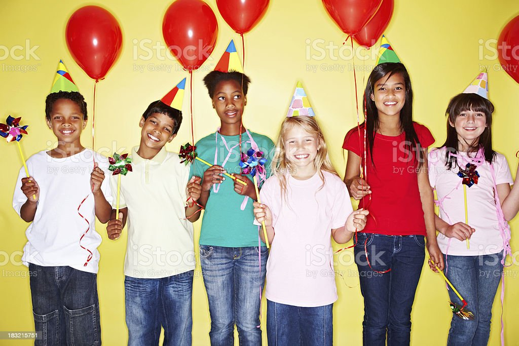 Happy multi racial kids holding red balloons against yellow royalty-free stock photo