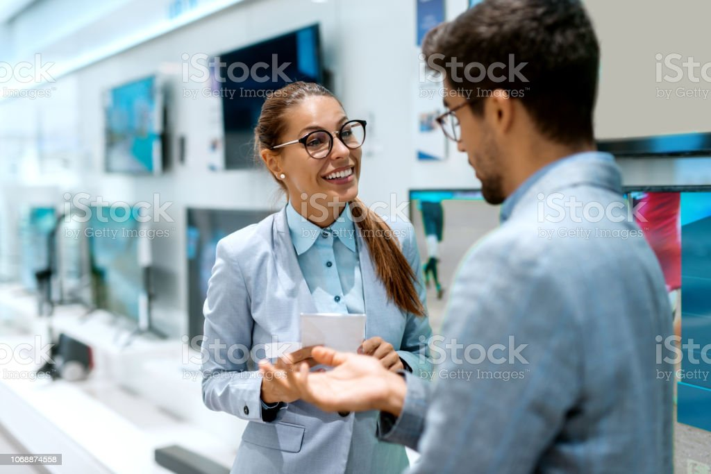Happy multicultural couple in formal wear talking about price for...