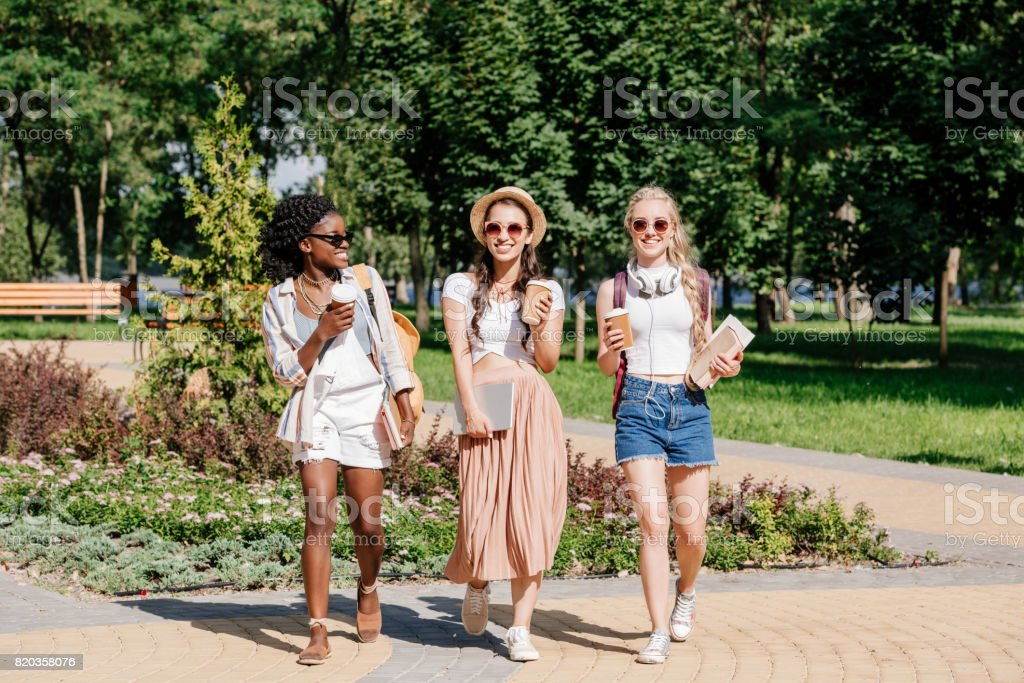 happy multicultural women with disposable cups of coffee in hands walking in park stock photo