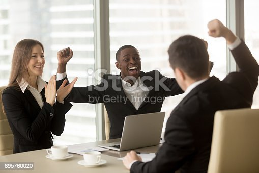 istock Happy multi-ethnic business team celebrating victory, raising hands and applauding 695760020