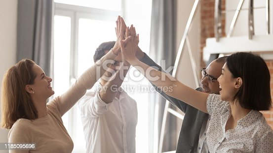 937843262 istock photo Happy multiethnic business team engaged in teamwork give high five 1185095696