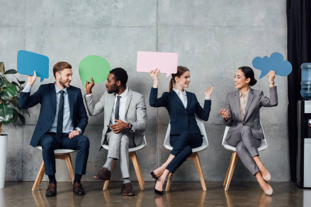 happy multiethnic businesspeople holding speech bubbles and thought bubble while sitting in waiting hall happy multiethnic businesspeople holding speech bubbles and thought bubble while sitting in waiting hall thought bubble stock pictures, royalty-free photos & images