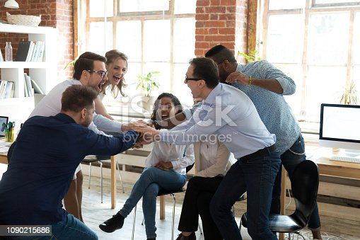 istock Happy multi-ethnic corporate employees join hands together at group meeting 1090215686