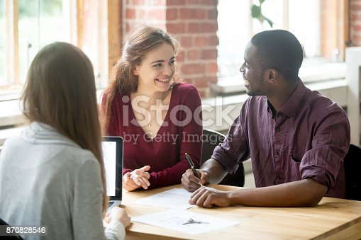 istock Happy multiethnic couple looking at each other before signing contract. 870828546