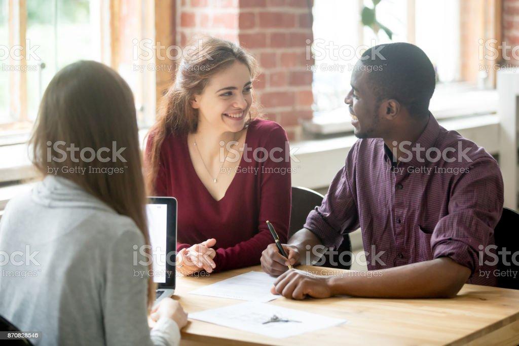 Feliz pareja multiétnica mirar antes de firmar contrato. - foto de stock