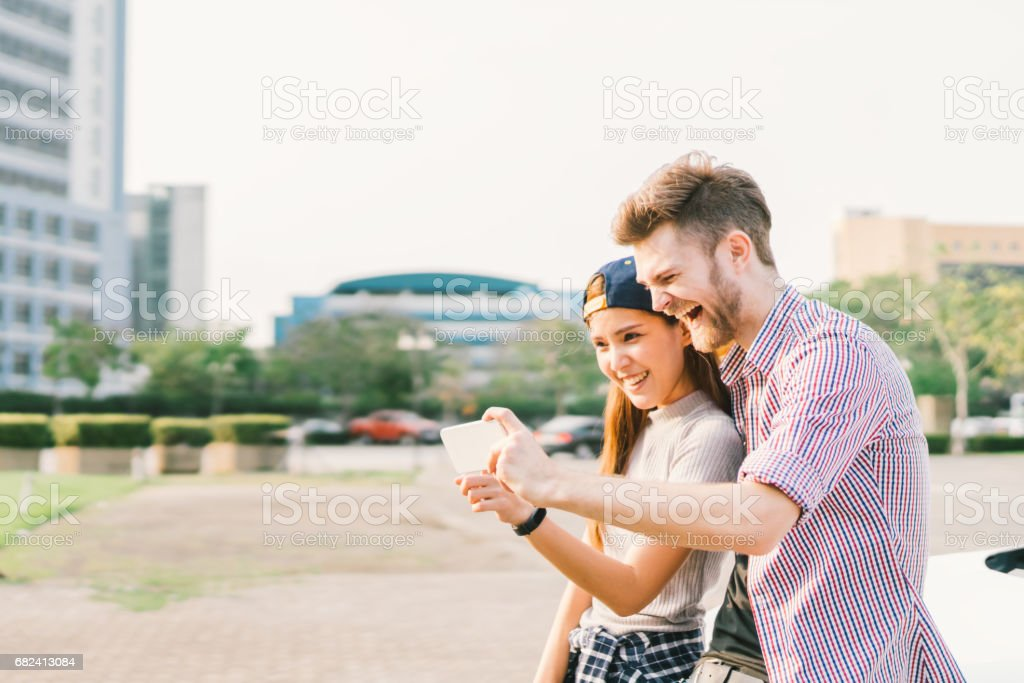 Happy multiethnic couple taking selfie during sunset in the city, fun and smiling, love or gadget technology concept royalty-free stock photo