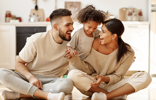 happy family multiethnic mother, father and son  laughing, playing,and tickles  on floor in cozy kitchen at home