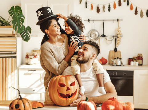 happy multiethnic family mother, father and little son have fun and celebrate Halloween at home
