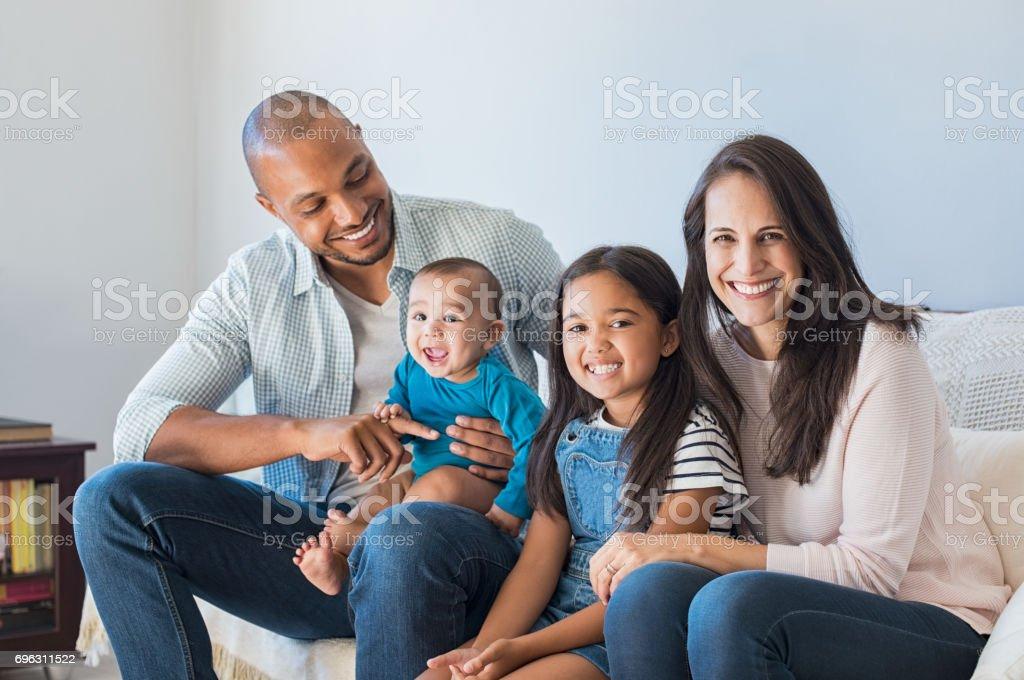 Happy multiethnic family on sofa stock photo