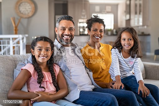 Portrait of cheerful ethnic family at home sitting on sofa and looking at camera. Happy indian family with two children relaxing at home. Mixed race parents with their daughters in new home.
