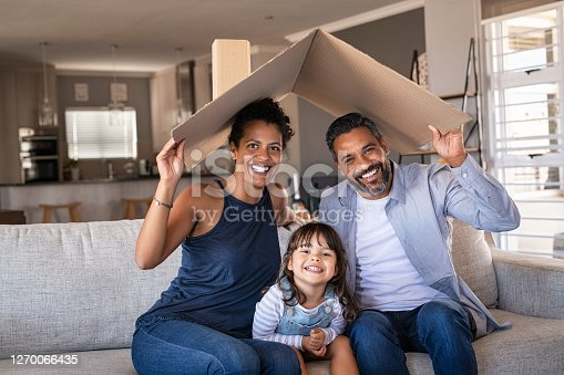 Portrait of smiling family sitting on couch holding cardboard roof and looking at camera. African and indian parents with funny daughter holding cardboard roof over heads while sitting on sofa in their new home. Happy mother and father with daughter in new house at moving day with copy space.
