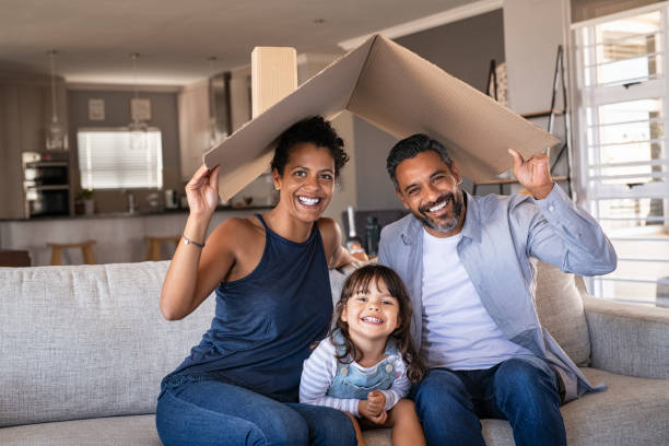 Happy multiethnic family with child holding cardboard roof stock photo